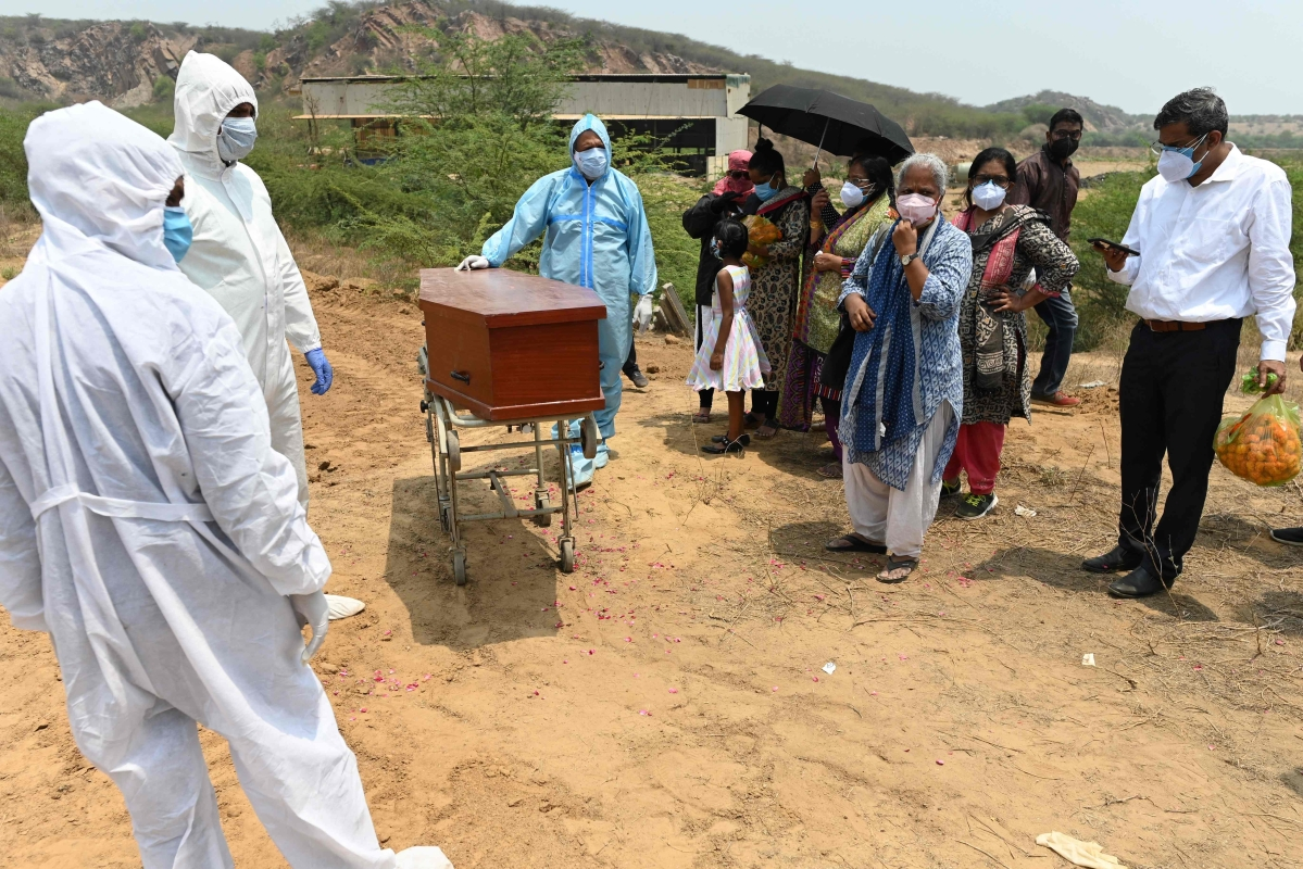 Employees of Michael Undertakers and Ambulance Services (L), seen wearing PPE suits, as relatives attend the burial of COVID-19 victim at a Christian cemetery in Pali village near Faridabad.