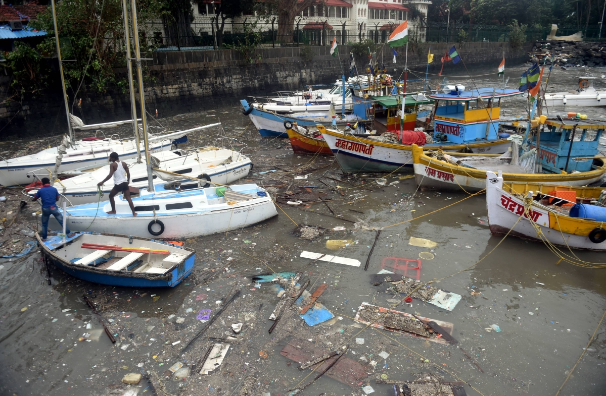 Garbage collects near the boats anchored at Gateway of India in Mumbai, Tuesday,