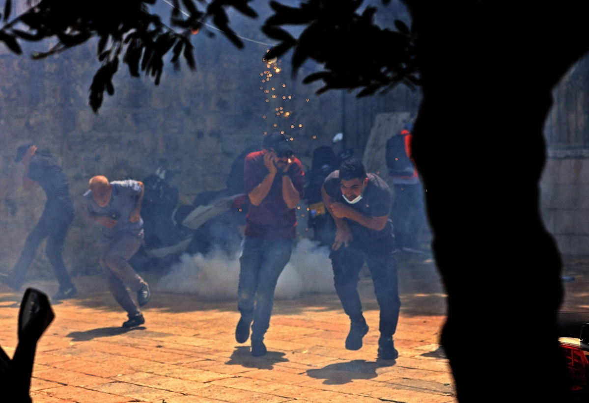 Palestinians run for cover from tear gas fired by Israeli security forces in Jerusalems Old City on May 10, 2021, ahead of a planned march to commemorate Israels takeover of Jerusalem in the 1967 Six-Day War.