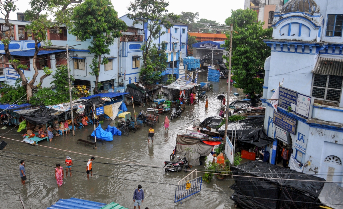 Pedestrians wade through a flooded road during landfall of cyclone Yaas, in Kolkata, Wednesday, May 26, 2021.