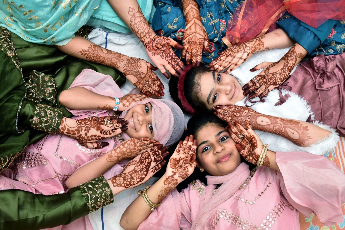 Girls pose for a photograph with Heena design on their hand during Eid-ul-Fitr festival marking the end of the holy fasting month of Ramadan, in Hyderabad on Friday.