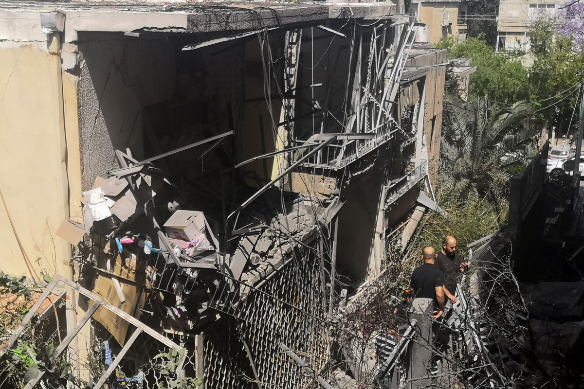 Israeli residents inspect a damaged house in the Tel Aviv suburb of Givatayim on May 12, 2021, following a nights rocket strike, the first in the neighbourhoods history. - Tel Aviv, 70 kilometres (40 miles) from Gaza City, had been largely spared the brunt of rockets fired by Palestinian militants in the territory, under Israeli blockade for 15 years.