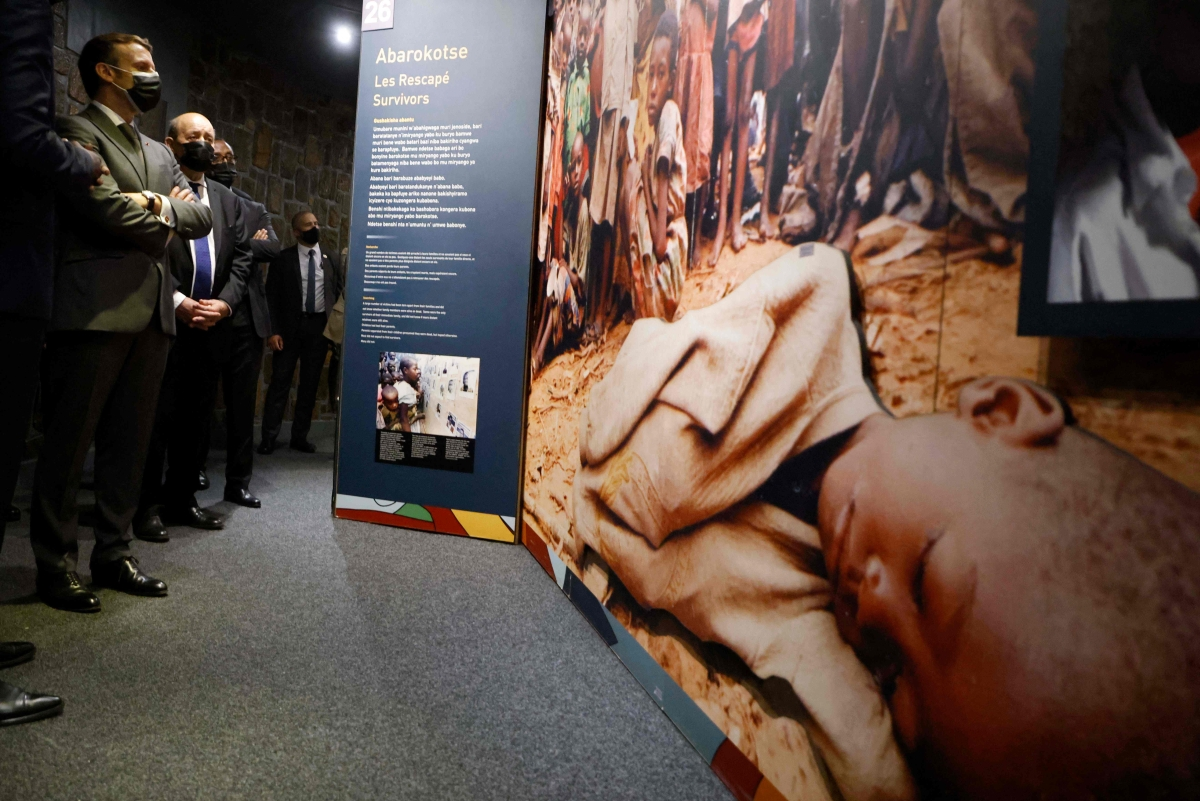 Macron (L) and French European and Foreign Affairs Minister Jean-Yves Le Drian stop to look at images during their visit to the Kigali Genocide Memorial, where some 250,000 victims of the massacres are buried, in Kigali on May 27