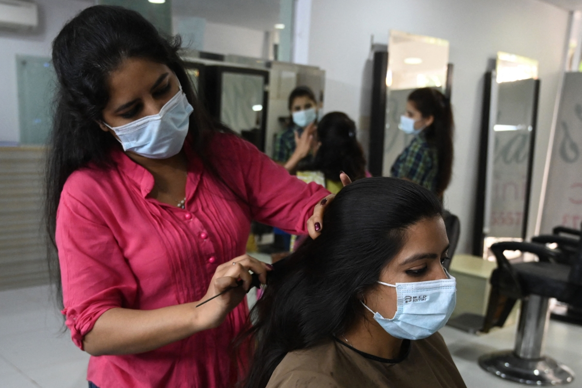A beautician attends a customer at a beauty salon during the holy month of Ramadan ahead of the Eid al-Fitr festivities amid the Coronavirus pandemic in Islamabad on May 10, 2021.