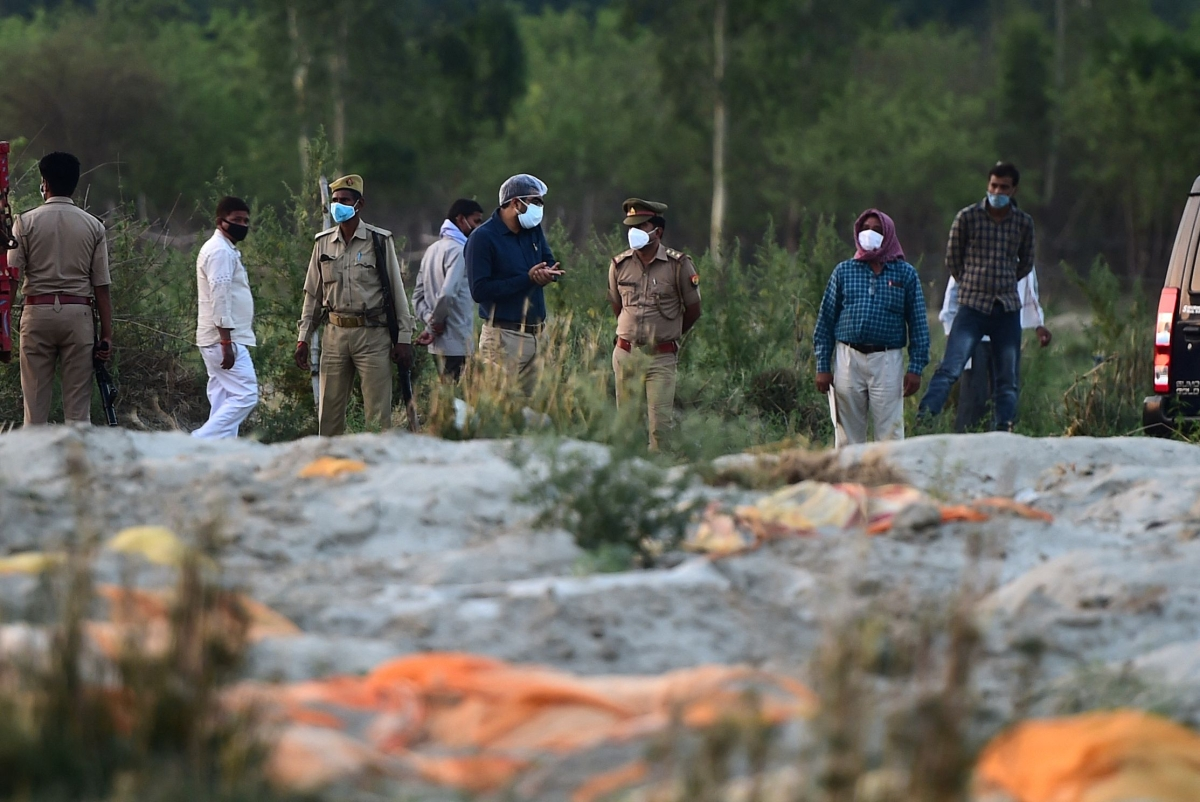 Police and administrative officials (background) inspect a cremation ground on the banks of Ganges River, where suspected bodies (foreground) of Covid-19 coronavirus victims appeared partially buried, at Rautapur Ganga Ghat in Unnao on May 13, 2021.
