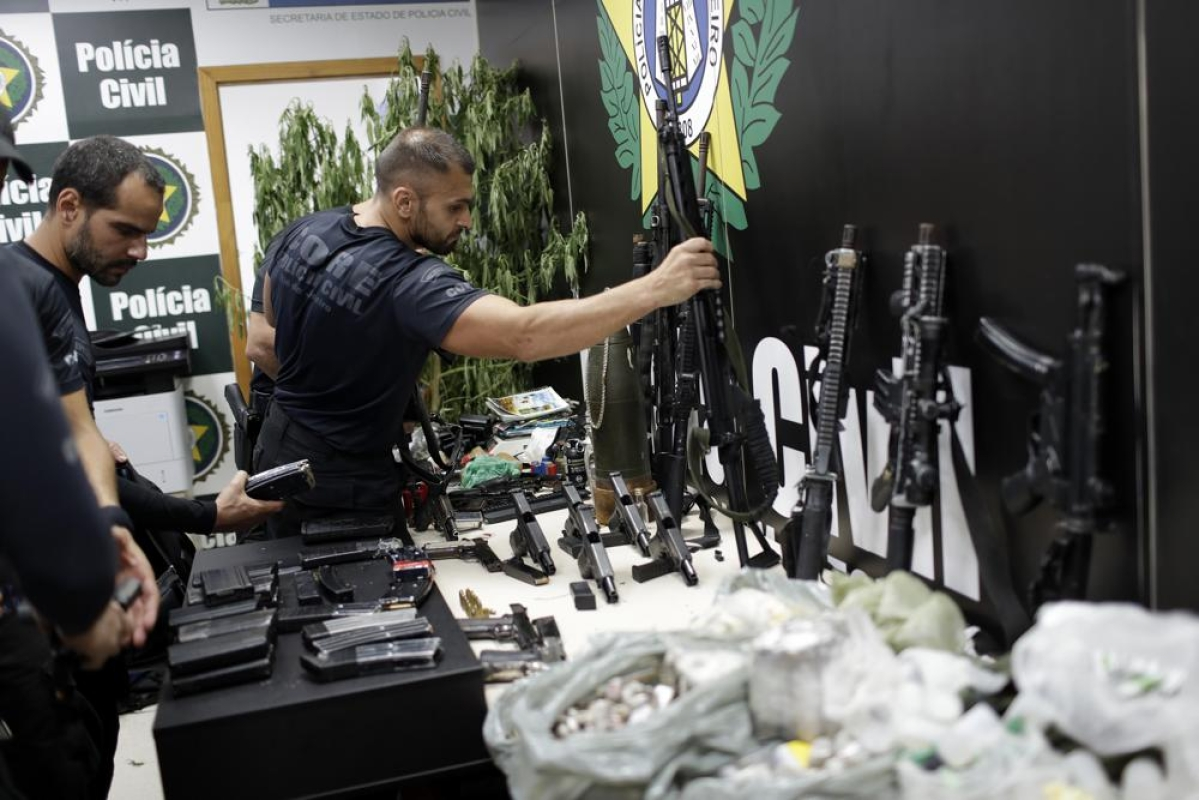 Policemen collect the drugs and weapons, allegedly seized during a police operation against drug dealers in Jacarezinho slum