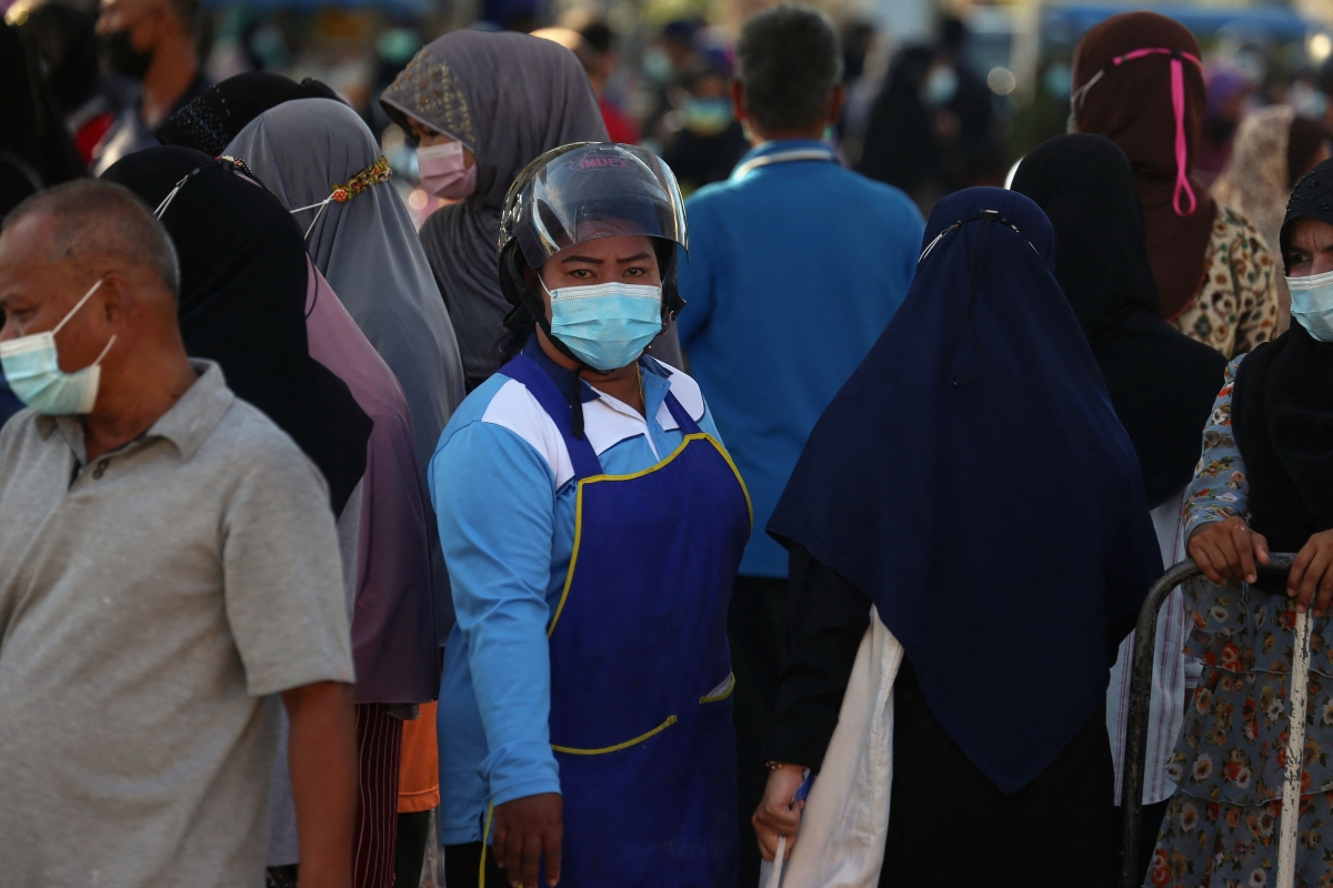 A vendor wearing a face mask and motorcycle helmet stands amongst a crowd of people visiting a fresh food market, busy for the Eid ul-Fitr festival marking the end of the Islamic holy month of Ramadan, amid concerns over the spread of the Coronavirus in Pattani on May 11, 2021.