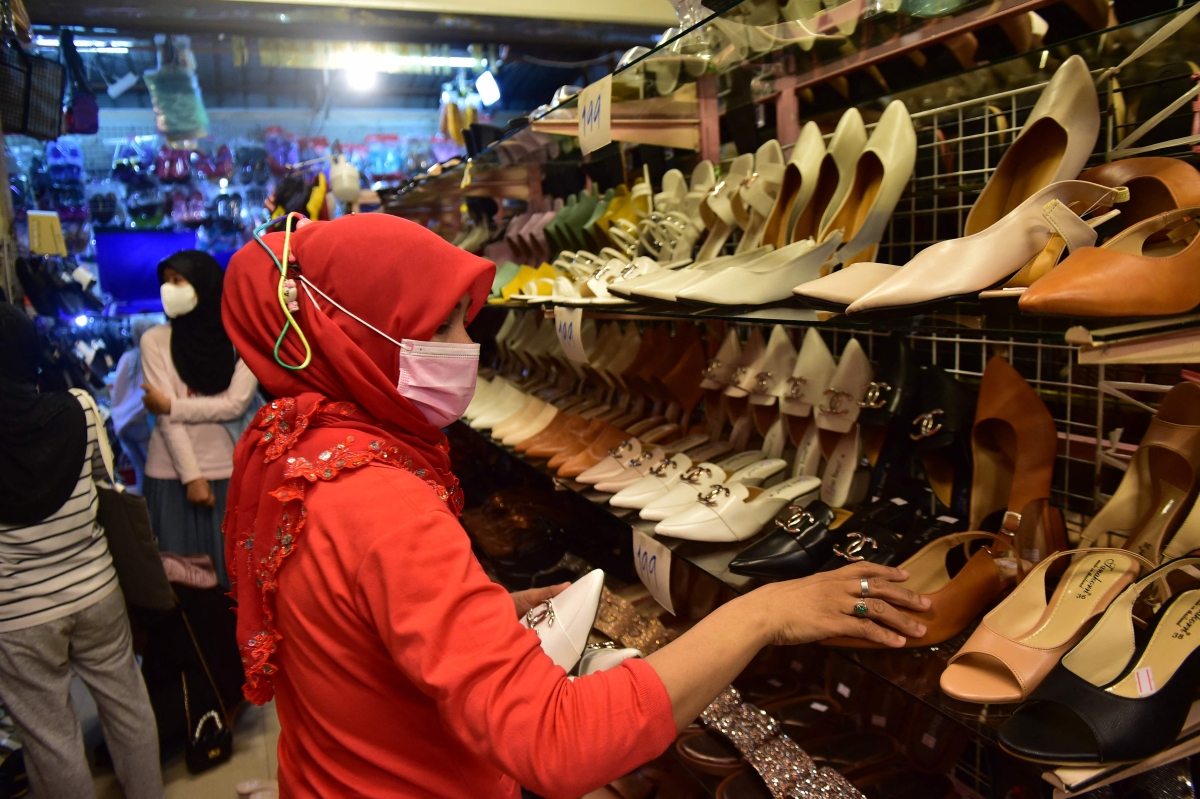 In this photo taken on May 9, 2021 a woman shops for shoes at a market amid concerns over the spread of the Coronavirus in the southern Thai province of Narathiwat, ahead of the Eid ul-Fitr festival marking the end of the Islamic holy month of Ramadan.
