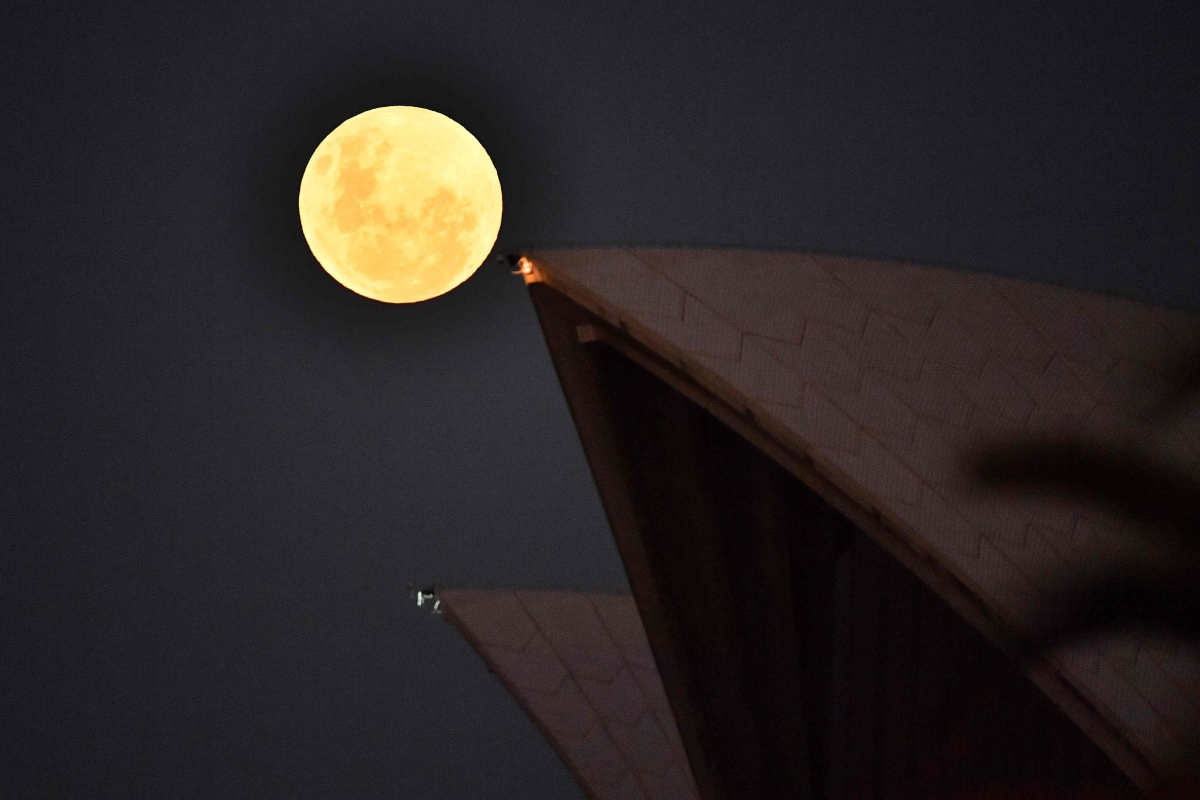 """The Moon rises over the Opera House in Sydney on May 26, 2021, ahead of a total lunar eclipse as stargazers across the Pacific are casting their eyes skyward to witness a rare """"Super Blood Moon""""."""