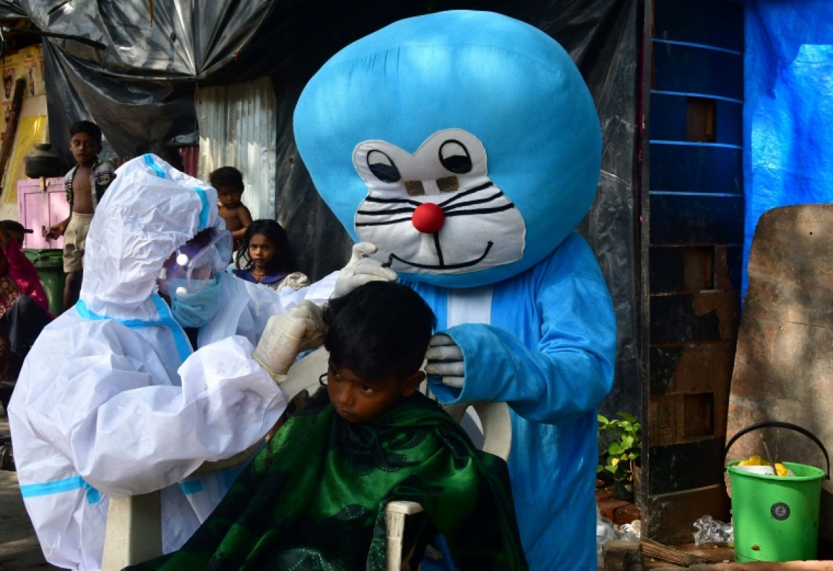 Barber giving haircut to a kid while a man dressed as Doraemon accompanies him