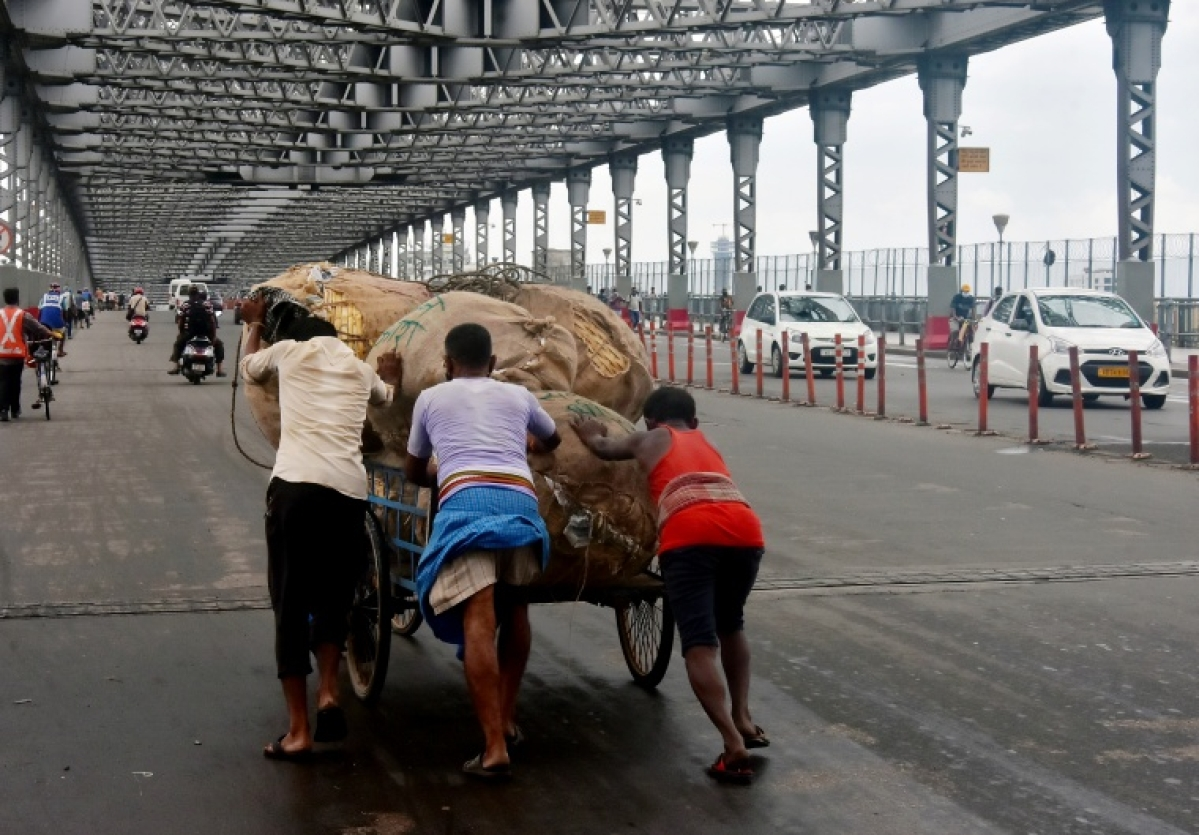 Workers push the cart loaded with a sack of goods at Howrah bridge in Kolkata on Tuesday