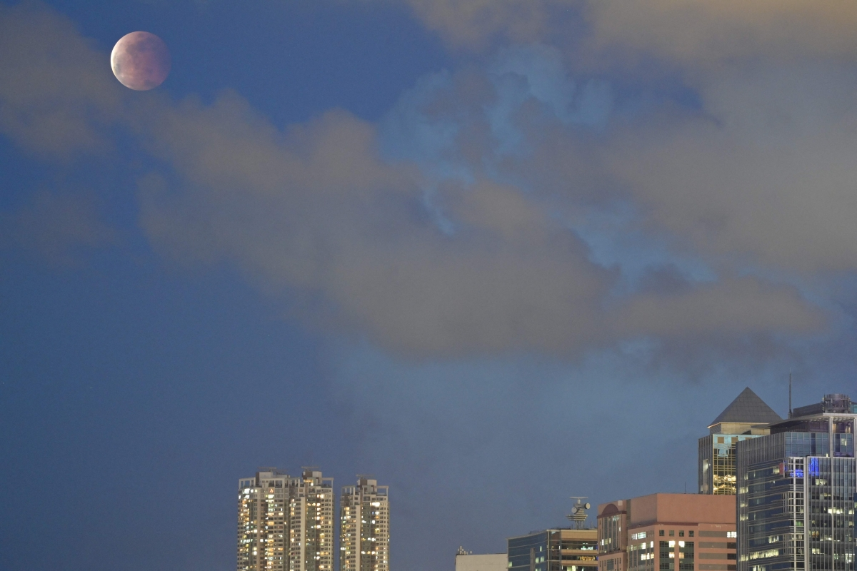 """The moon is pictured above Hong Kong on May 26, 2021, during a total lunar eclipse as stargazers across the Pacific are casting their eyes skyward to witness a rare """"Super Blood Moon""""."""