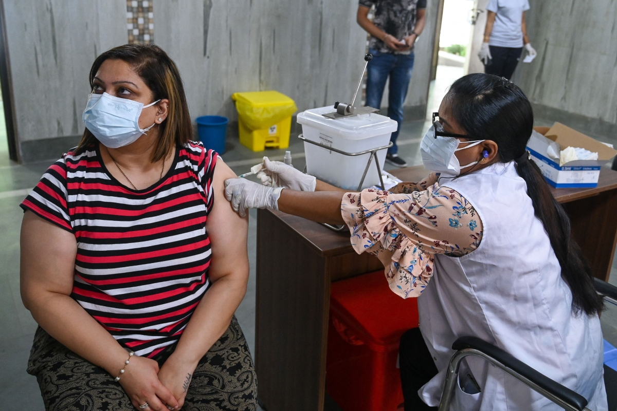 A health worker inoculates a woman with a dose of the Covishield Covid-19 coronavirus vaccine at a vaccination centre in New Delhi on May 13, 2021.