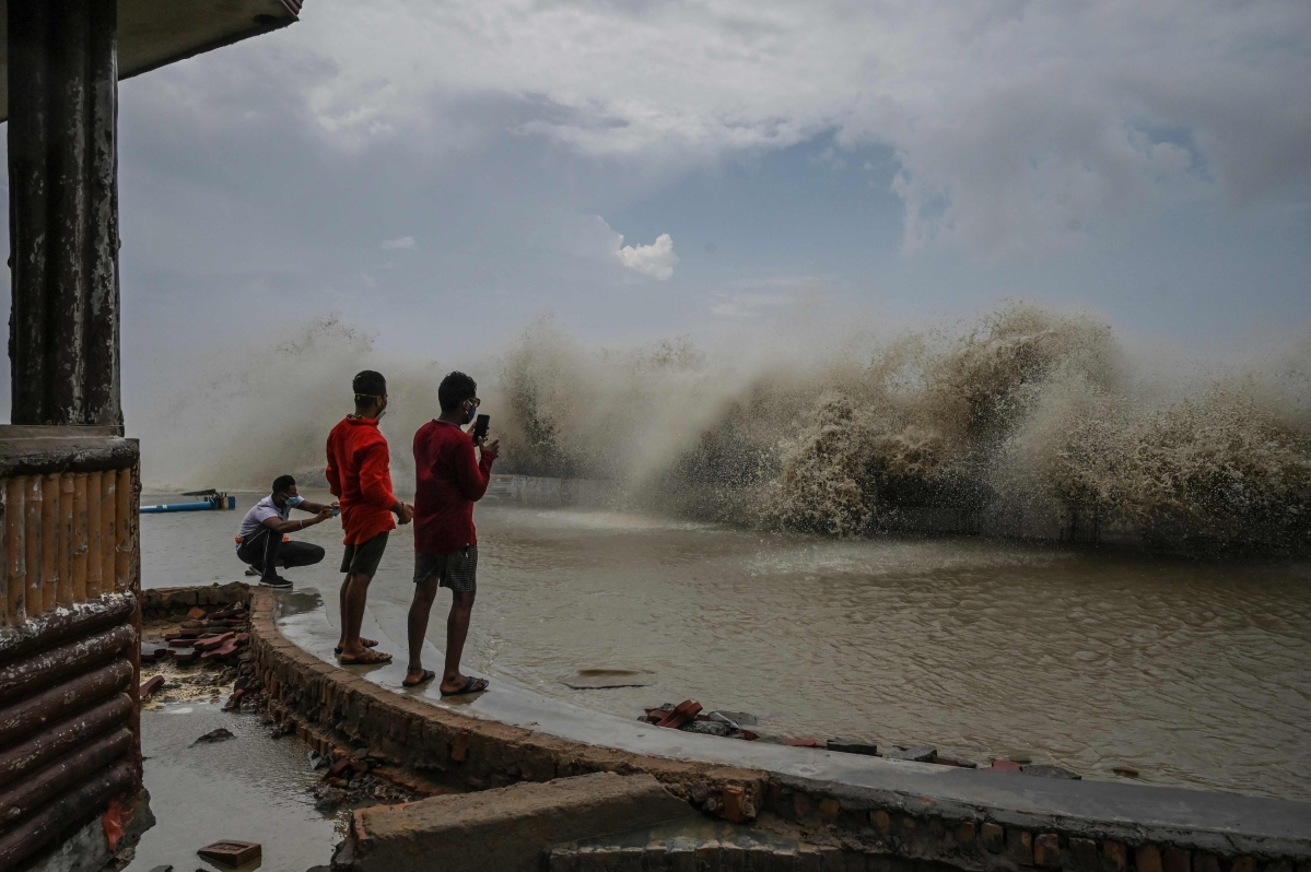 Residents take pictures of waves lashing onto a shoreline after Cyclone Yaas hit Indias eastern coast in the Bay of Bengal in Digha, some 190 km from Kolkata on May 27, 2021.