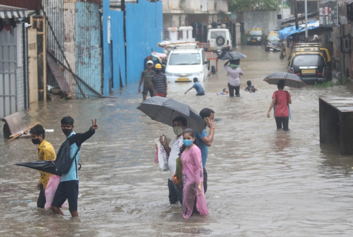 People trying to make their way throuh a road waterlogged in the city due to heavy rains