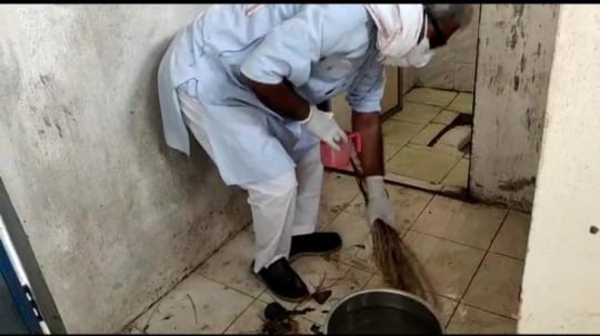 MP Janardan Mishra cleaning toilet at Kunj Bihari Covid care Centre in Rewa on Monday
