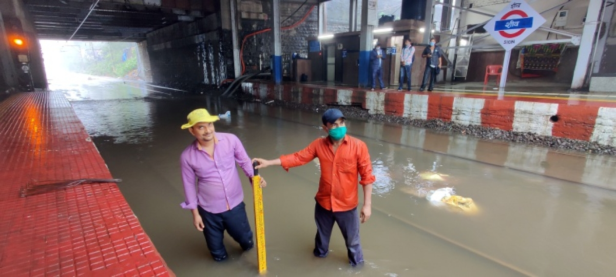 Railway workers at waterlogged Sion station