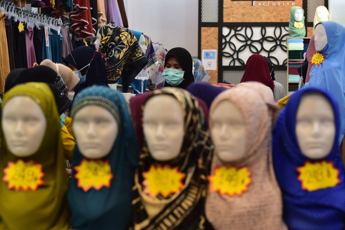 In this photo taken on May 9, 2021 a woman shops for clothes at a market amid concerns over the spread of the Coronavirus in the southern Thai province of Narathiwat, ahead of the Eid ul-Fitr festival marking the end of the Islamic holy month of Ramadan.