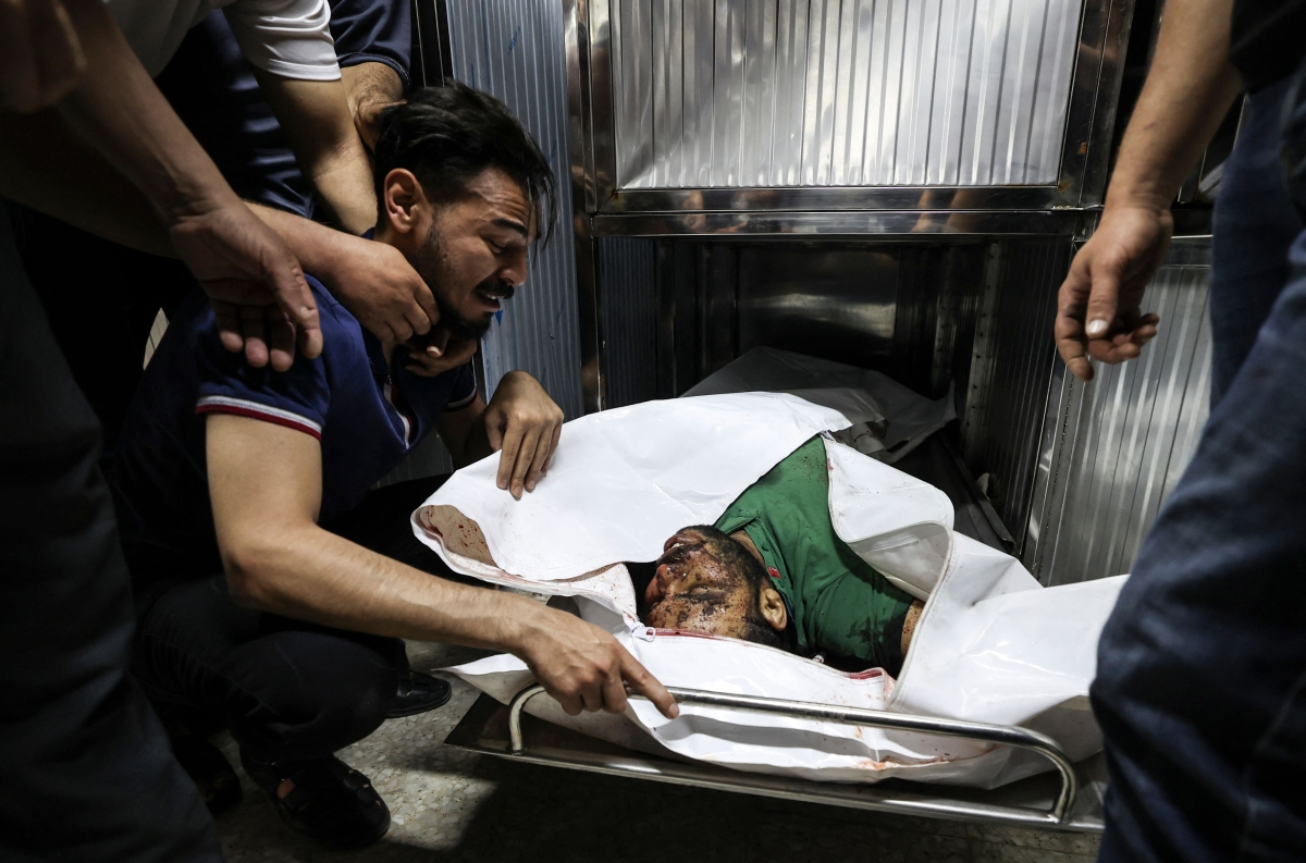 """A Palestinian mourns over the body of a relative in the mortuary of Al-Shifa Hospital in Gaza city following Israeli airstrikes on targets in the Gaza Strip, on May 12, 2021, amid the most intense Israeli-Palestinian hostilities in seven years. - Israels Defence Minister Benny Gantz vowed more attacks on Palestinian militant groups in Gaza to bring """"total, long-term quiet"""" before considering a ceasefire."""