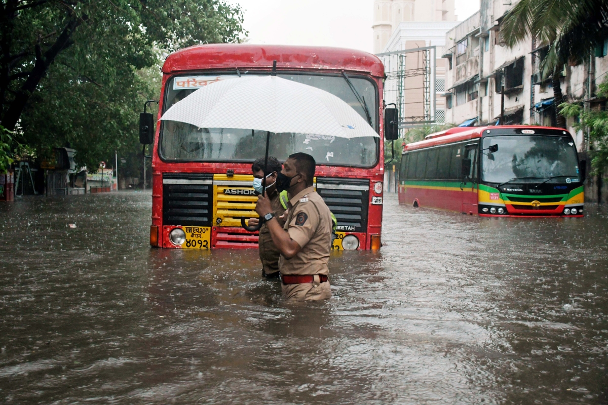 Police personnel carries an umbrella as he wades through a waterlogged street after heavy rainfall and strong winds triggered by Cyclone Tauktae, in Mumbai on Monday.