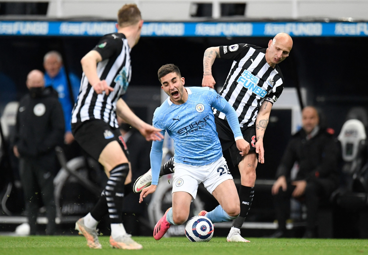 Newcastle United's English midfielder Jonjo Shelvey (R) fouls Manchester City's Spanish midfielder Ferran Torres during the match, at St James' Park on Friday