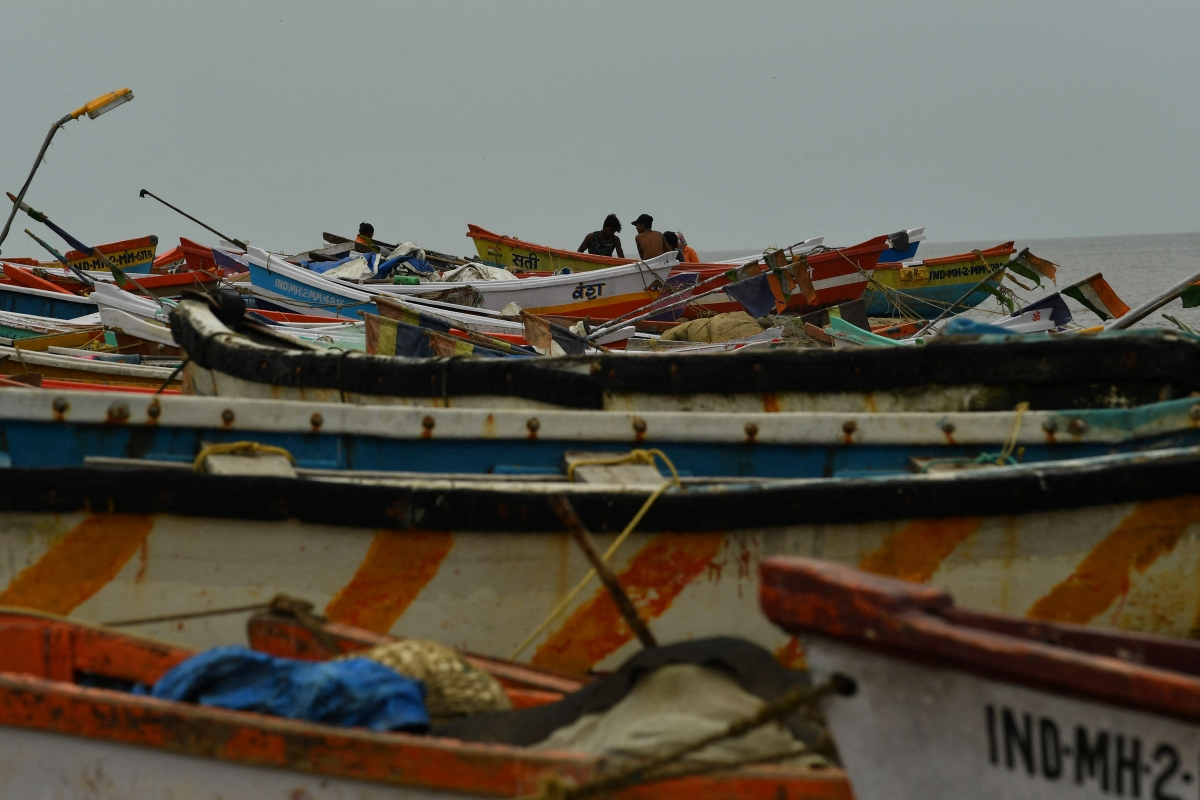 Fishermen are seen next to boats being moored at a fishing village off the city coast in the wake of the impending cyclone Tauktae in Mumbai on May 16, 2021.