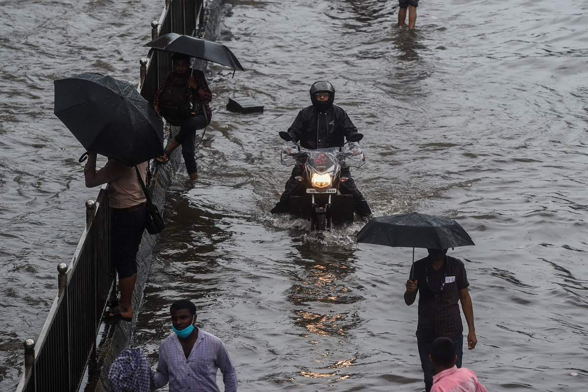 Commuters make their way through flooded roads following heavy monsoon rains in Mumbai on June 9, 2021.
