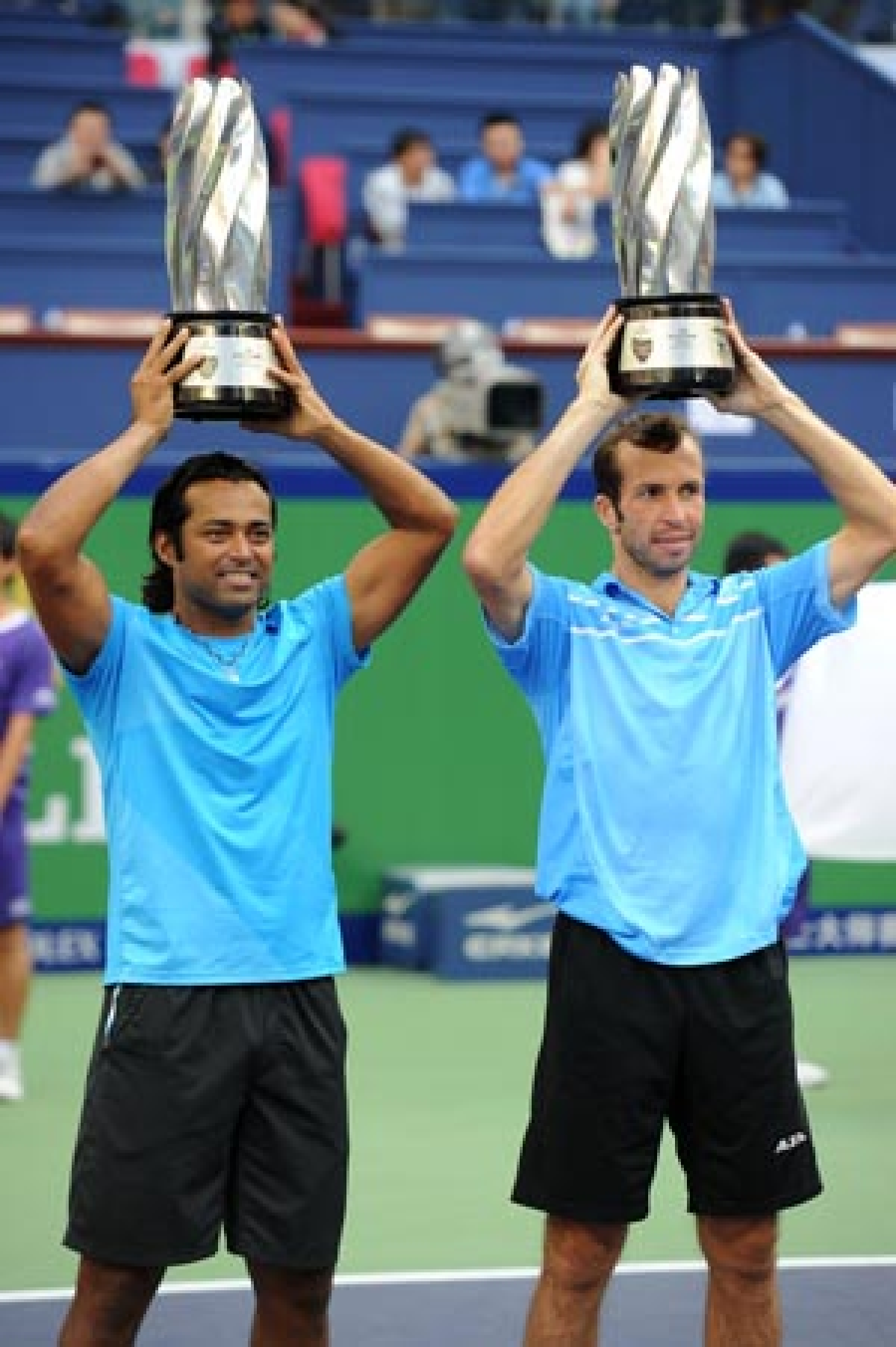 Leander Paes of India and Radek Stepanek of the Czech Republic hold their trophies after beating Mahesh Bhupathi and Rohan Bopanna of India in the doubles final of the Shanghai Masters tennis tournament in Shanghai on Sunday.