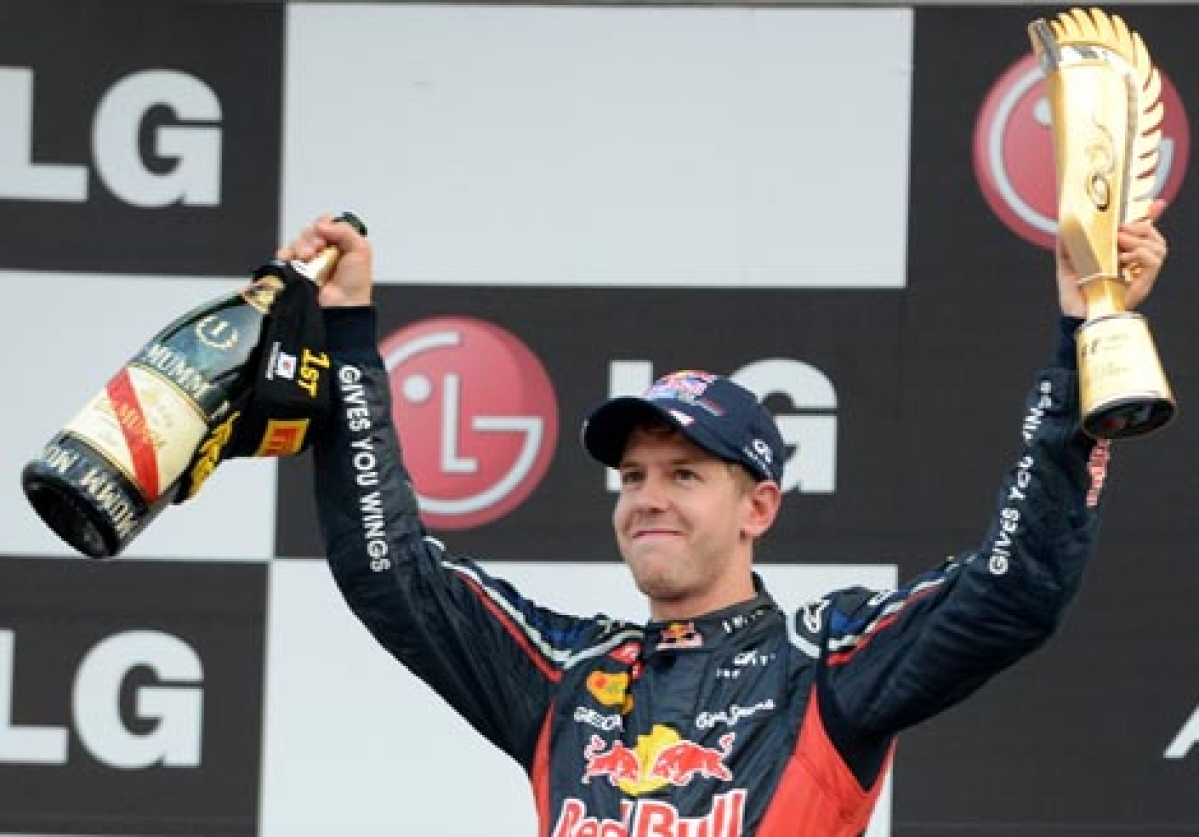 Sebastian Vettel lifts the Formula One Korean Grand Prix winner's trophy and a bottle of champagne on the podium at the Korean Circuit in Yeongam on Sunday.