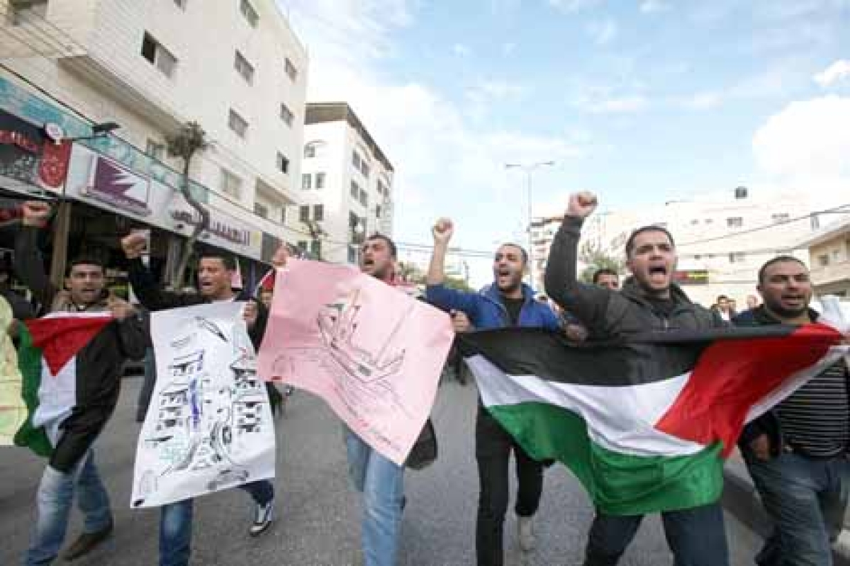 Hundreds of students from Hebron University some shouting and holding up the Palestinian flag demonstrate against the Israeli military attacks on the Palestinian Gaza strip, in the West Bank town of Hebron.