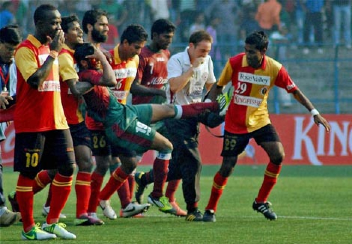 Mohuin Bagan players carry injured Syed Rahim Nabi, who was hit by a stone hurled by an East Bengal fan.