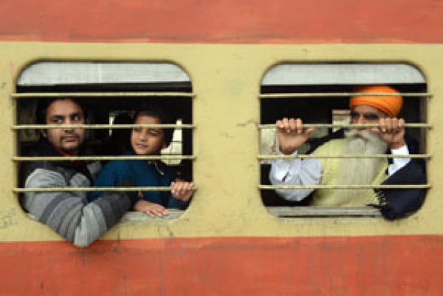 Passengers travel on a local train at the railway station in Amritsar on Tuesday