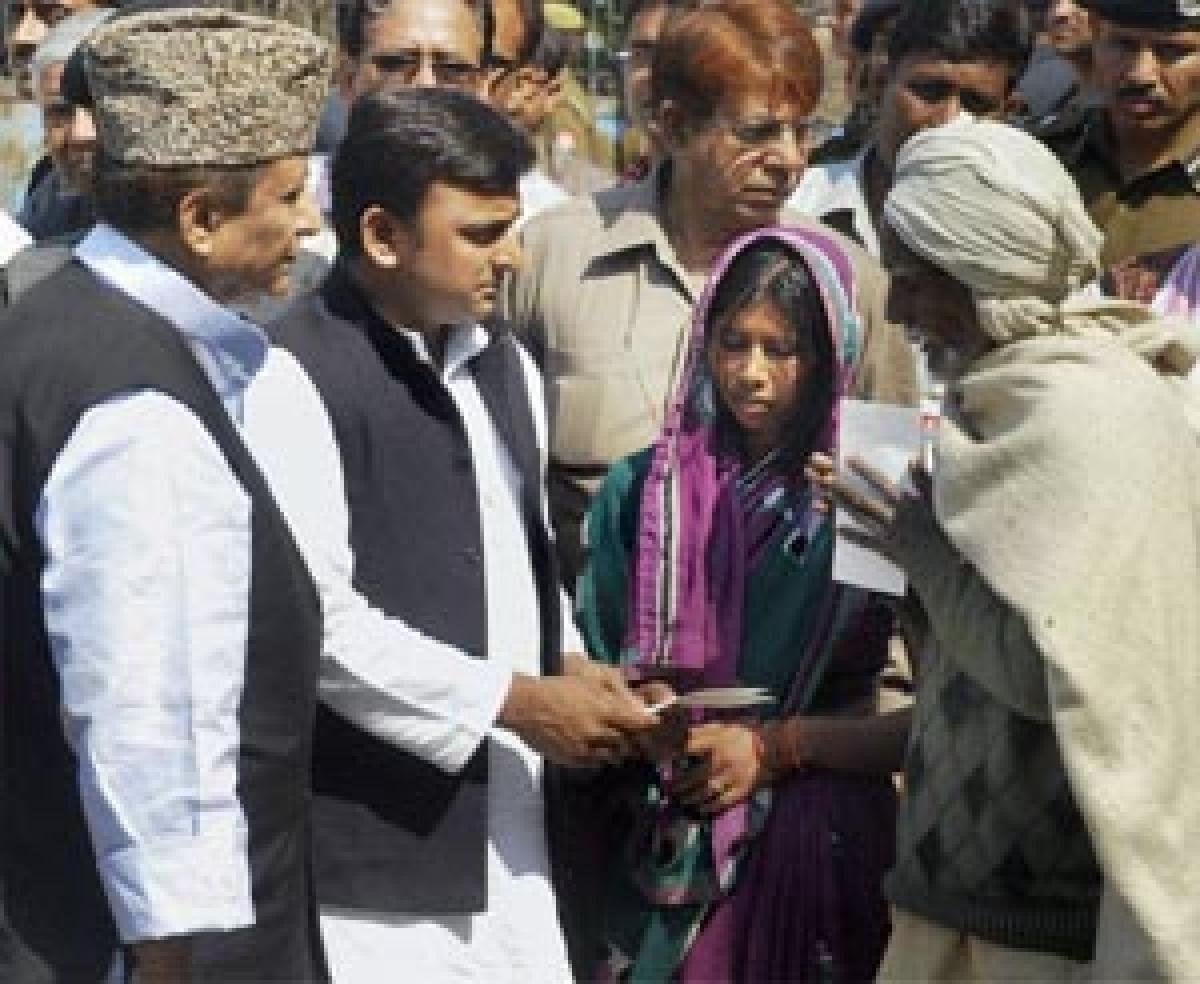 Uttar Pradesh CM Akhilesh Yadav presents a cheque to the family of slain village head Nanhe Yadav at Balipur village in Kunda, Pratapgarh.