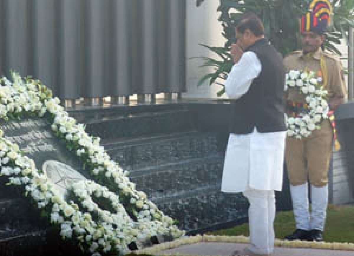 Chief Minister Prithviraj Chavan pays his respects while (below) relatives pay homage to the martyrs and victims at a memorial at Police Gymkhana
