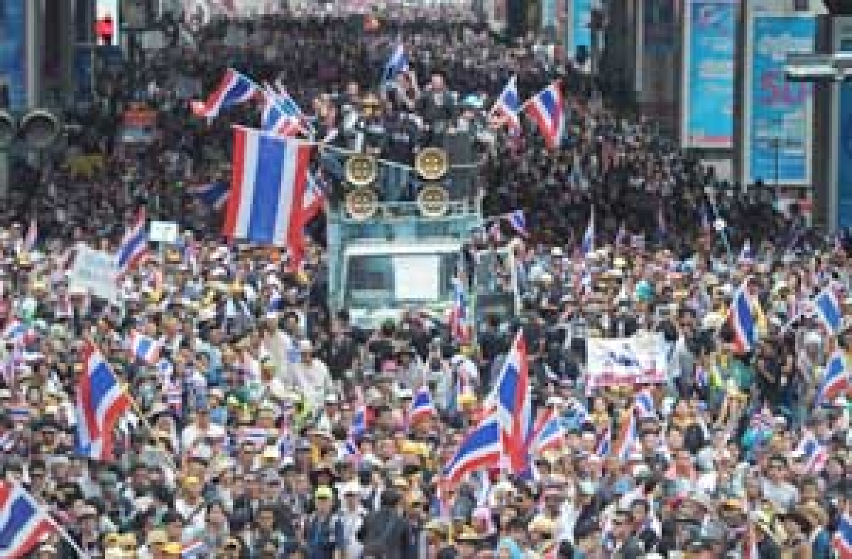 Anti-government protesters wave national flags during a demonstration in Bangkok earlier on Monday.