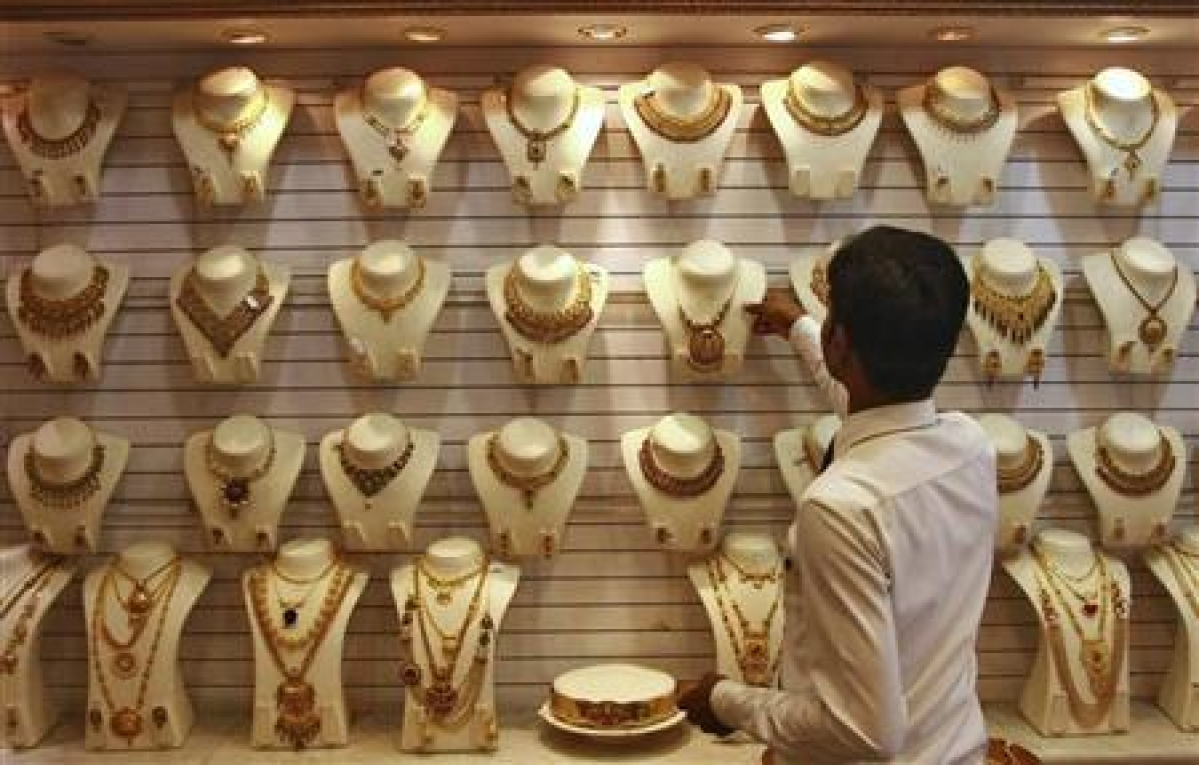 Gold falls on selling by stockists amid weak demand