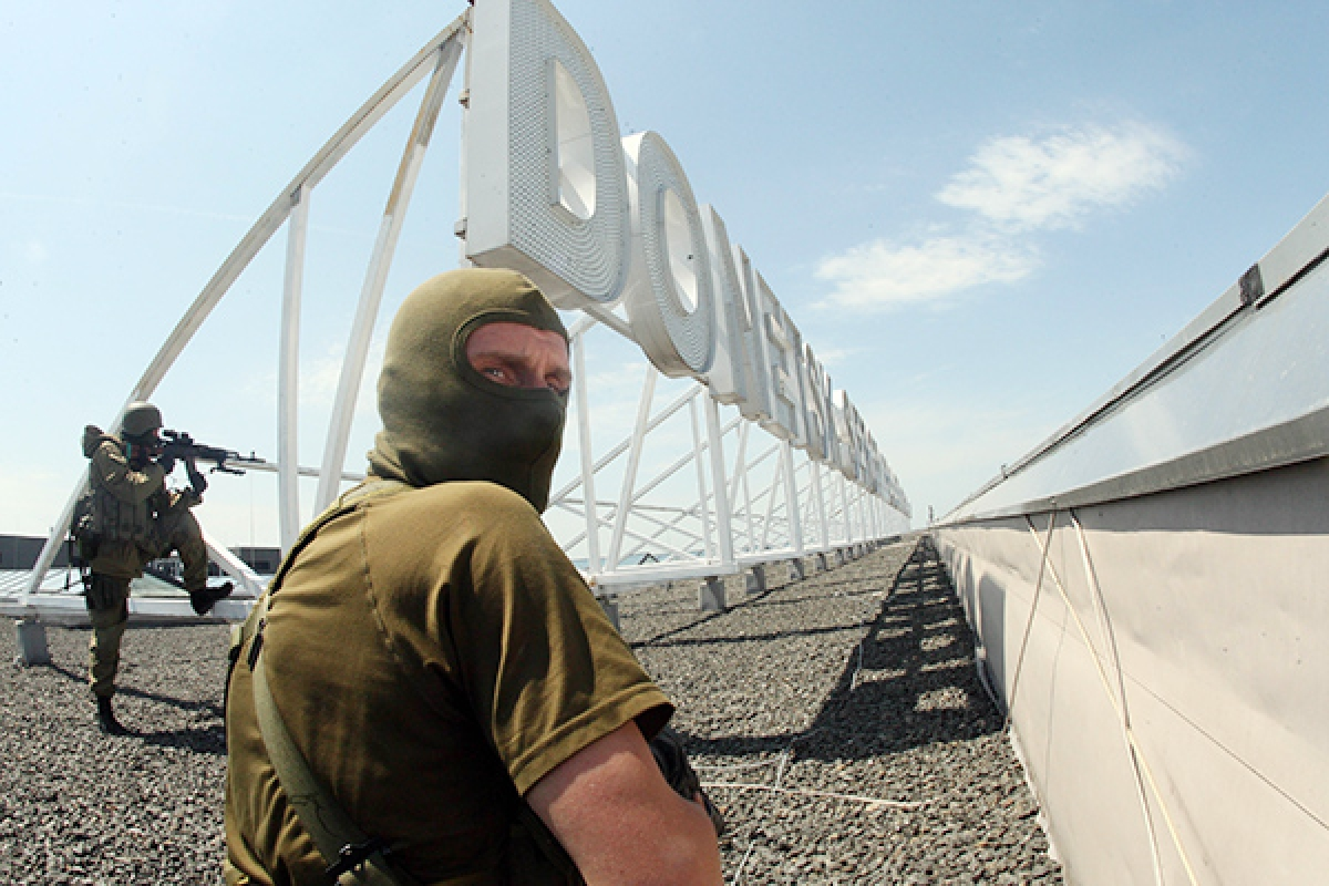 Pro-Russian militants take position on the roof of the Donetsk airport on Monday