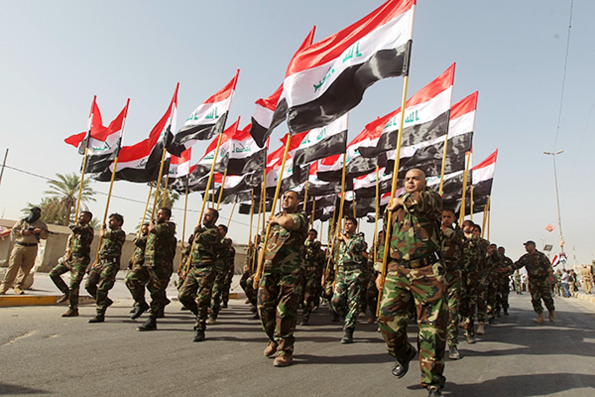 Newly-recruited Iraqi volunteers, holding national flags take part in a parade in Baghdad.