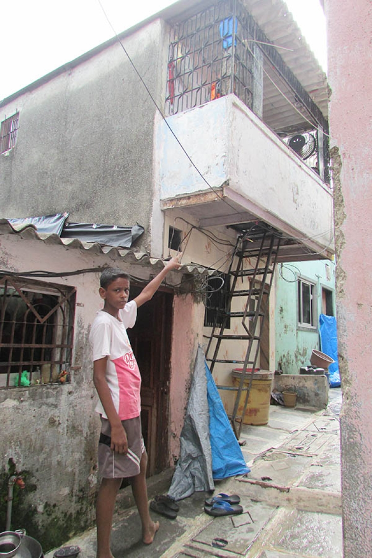 A neighbour points toward the house where the molestation victim set herself ablaze