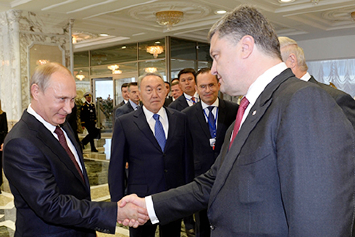 Putin  and Ukraine's President Poroshenko (R) shake hands during a summit in Minsk.