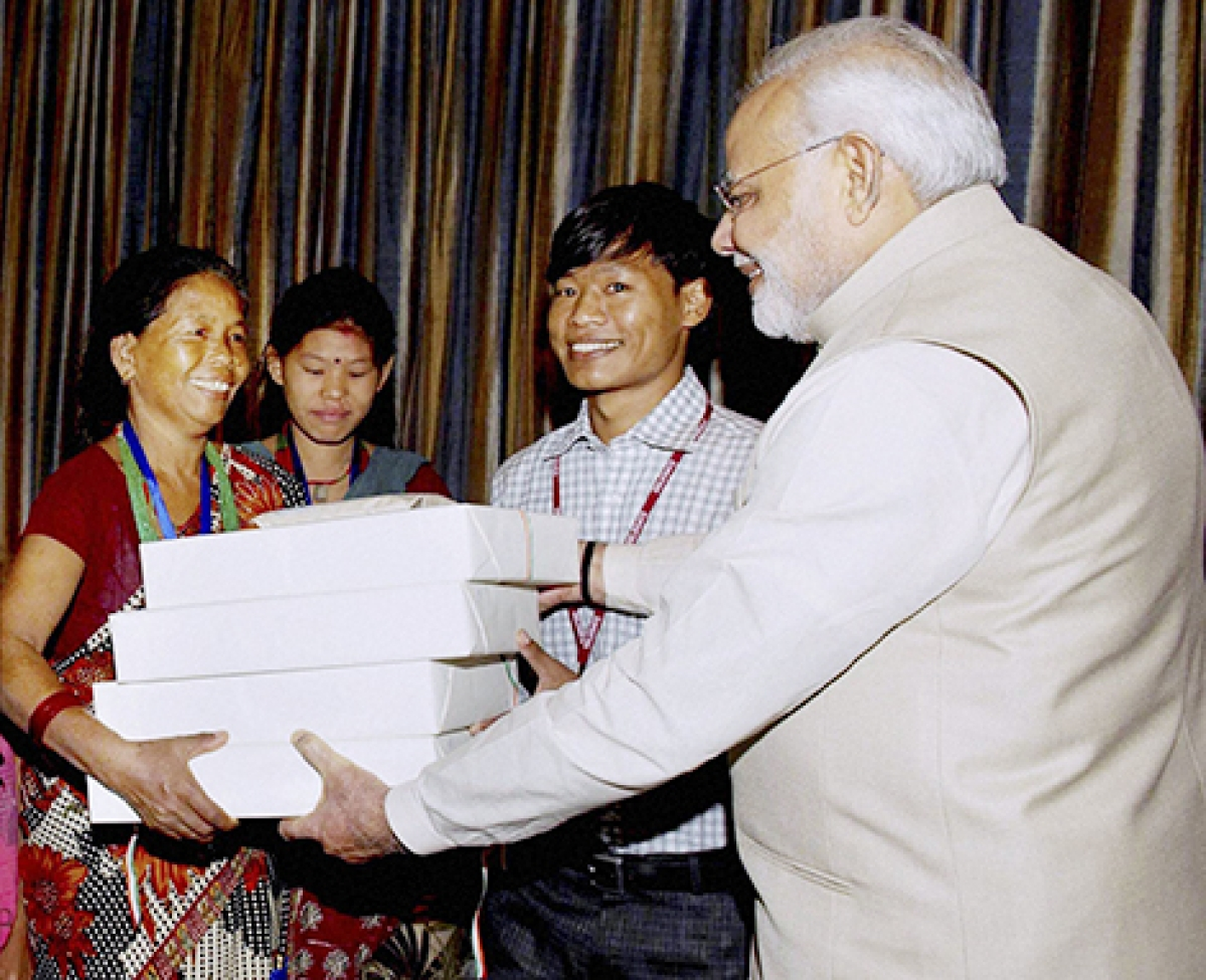 Prime Minister Modi giving presents to the family of Jeet Bahadur (2R) in Kathmandu, Nepal.