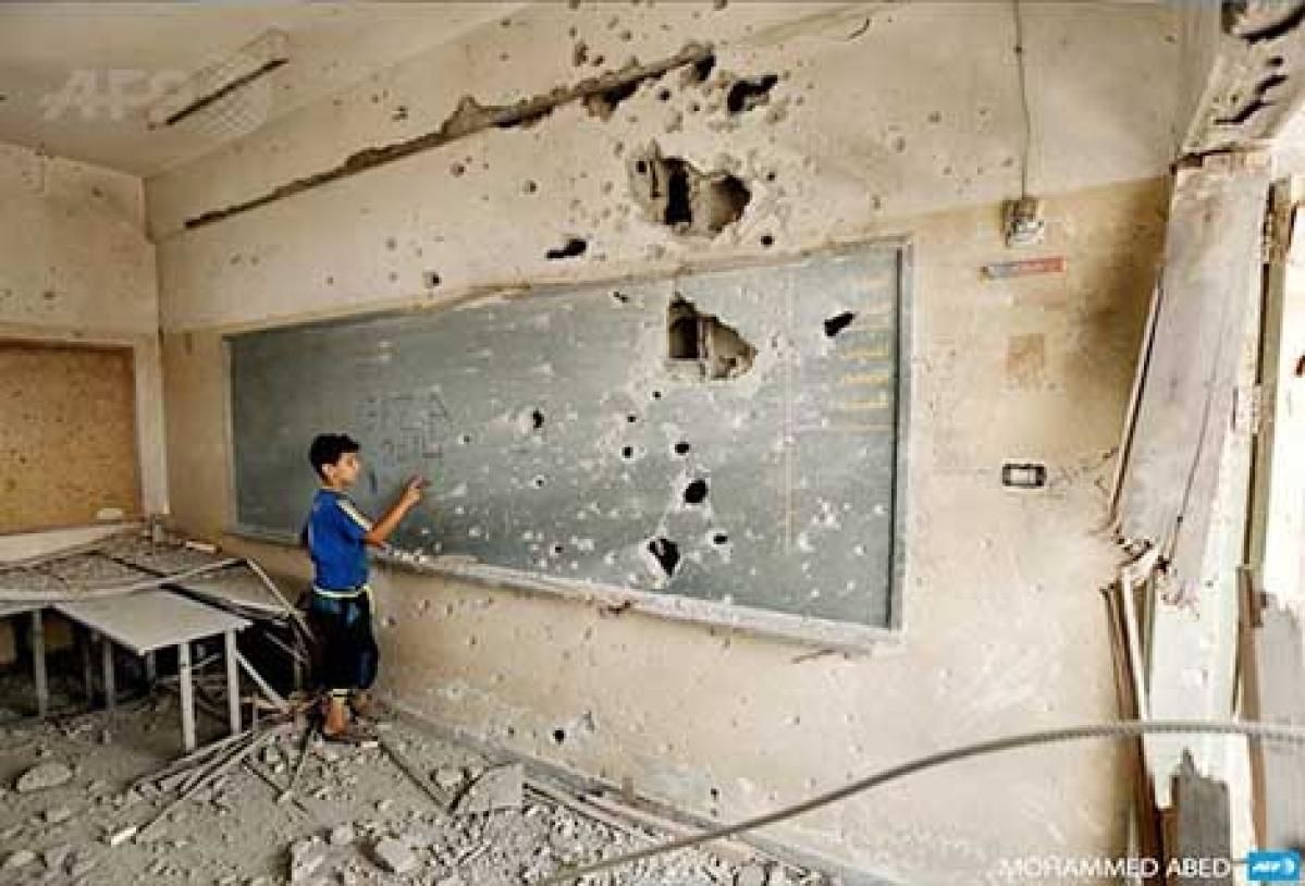 A Palestinian boy writes on a shrapnel-riddled backboard at a school in Gaza city.