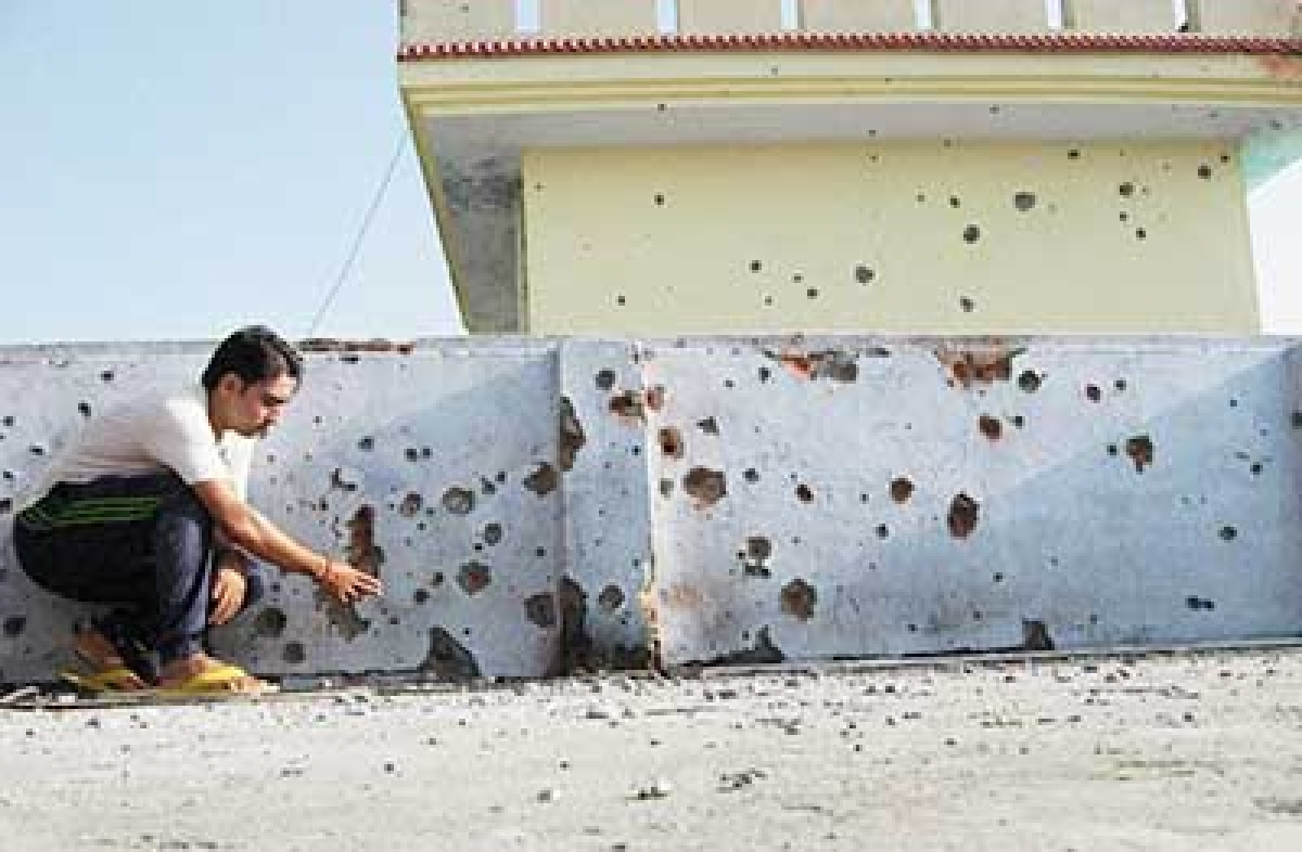 A man shows mortar shell marks on the wall of his house after shelling from the Pakistani side at Lalyal Camp Kanachak sector in Jammu on Thursday.