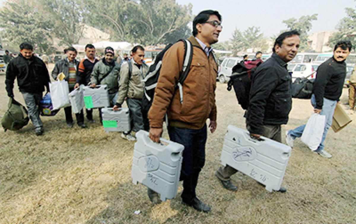 Polling officials leave for polling stations with EVMs ahead of the 5th phase of J&K Assembly elections in Jammu on Friday.