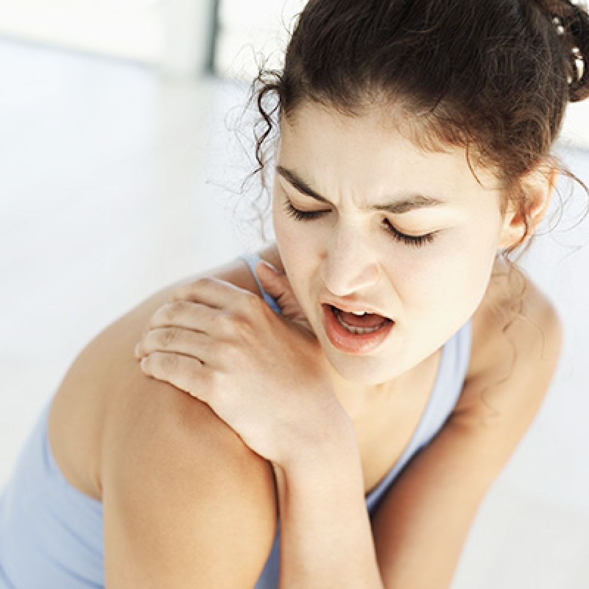 high angle view of a young woman holding her shoulder in pain