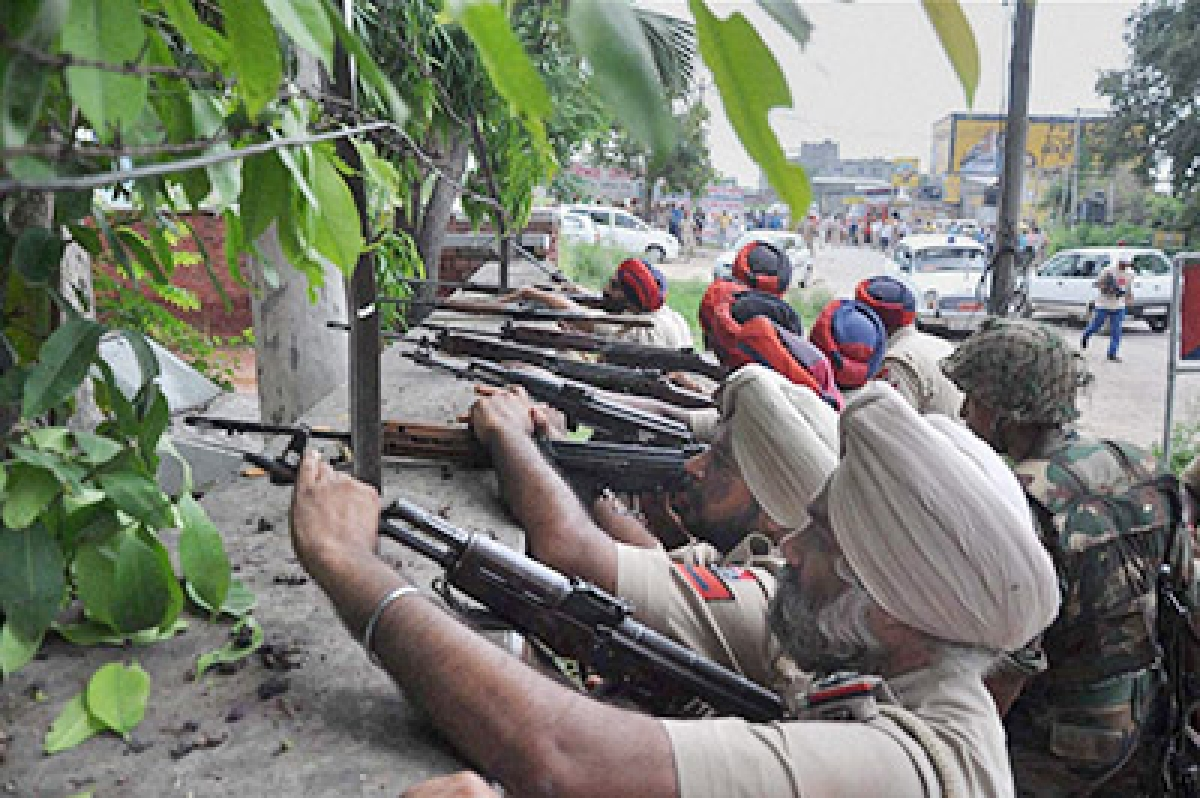 Gurdaspur: Police personnel take positions during an encounter with armed militants in Dinanagar town in Gurdaspur District of Punjab, on Monday. PTI Photo(PTI7_27_2015_000133B)
