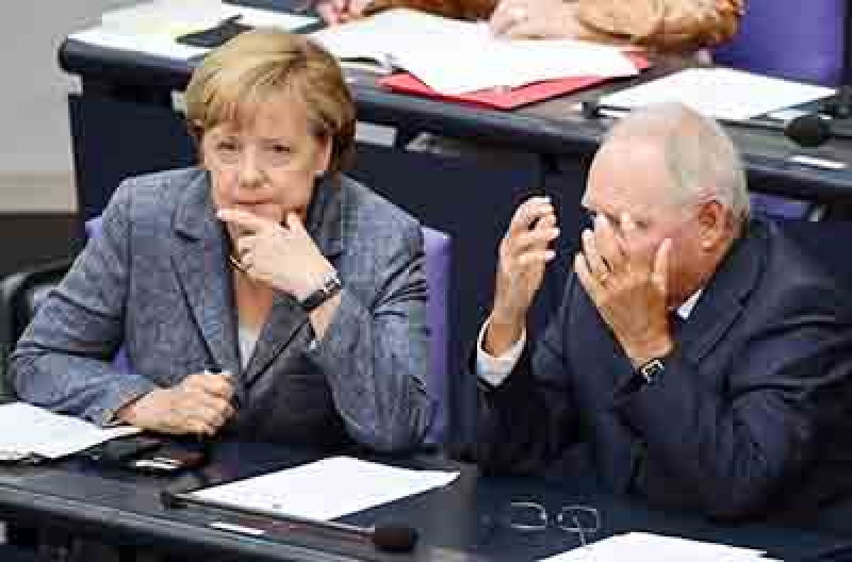 German Chancellor Angela Merkel (L) talks with German Finance Minister Wolfgang Schaeuble during a debate ahead of a vote on a third bailout for debt-mired Greece at German lower house of parliament (the Bundestag) in Berlin on August 19, 2015.  AFP PHOTO / JOHN MACDOUGALL
