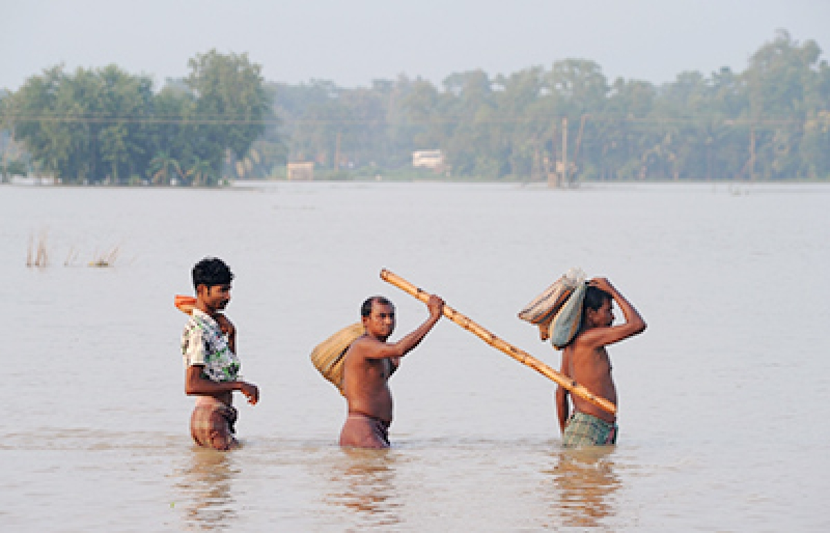 Indian men walk through a flooded area of Udaynarayanpur in Howrah district, west of Kolkata, on August 4, 2015.  Floods from days of torrential rain have now claimed at least 180 lives in India with one million people sheltering in relief camps after fleeing surging waters, officials said August 4.   Rivers have burst their banks, hitting thousands of villages in parts of West Bengal as well as northeastern Manipur state, where roads and bridges have been cut and communications were patchy. AFP PHOTO