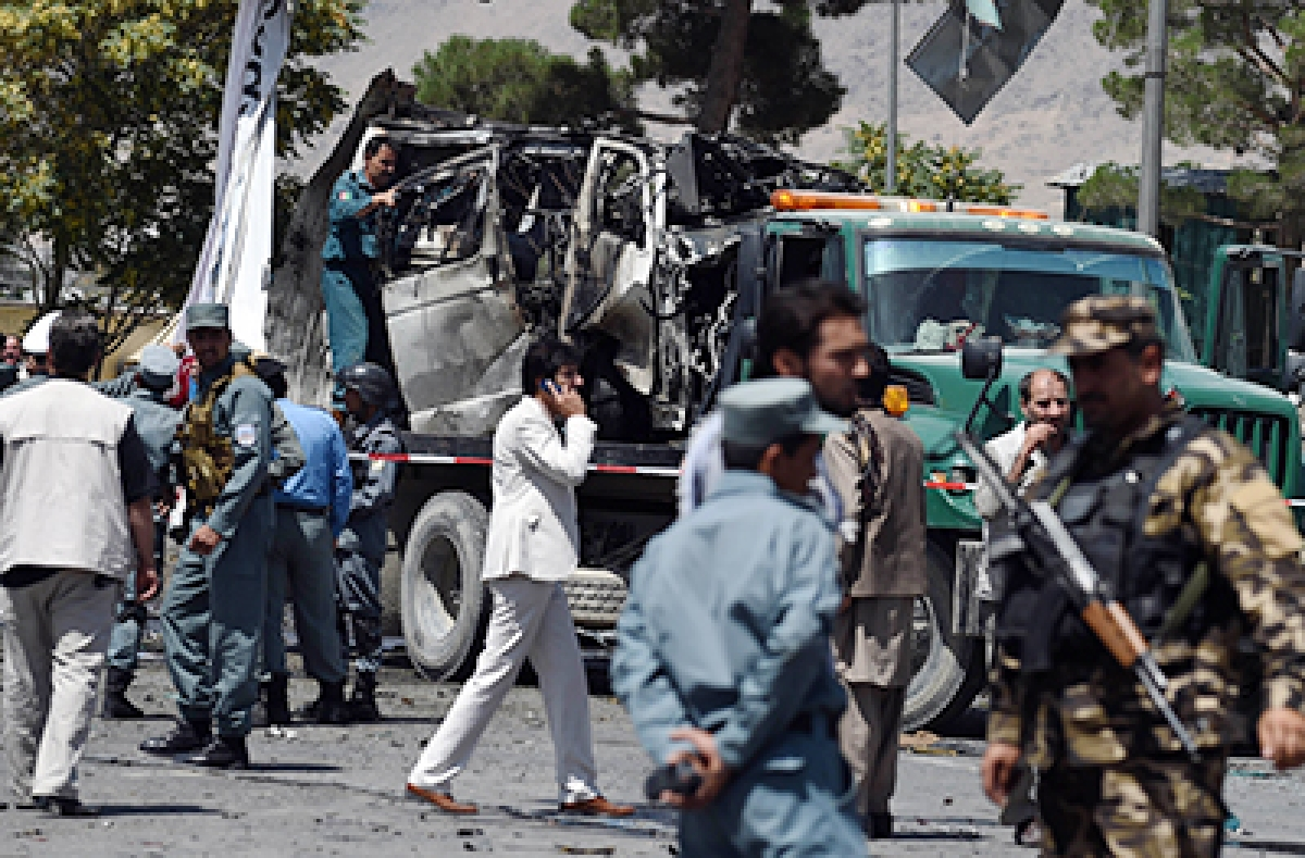 """Afghan security forces inspect a damaged vehicle at the site of a bomb attack near the entrance to Kabul's international airport in Kabul on August 10, 2015. A huge blast struck near the entrance of Kabul's international airport on August 10 during the peak lunchtime period, officials said, warning that heavy casualties were expected. """"The explosion occurred at the first check point of Kabul airport,"""" said deputy Kabul police chief Sayed Gul Agha Rouhani. AFP PHOTO / Wakil Kohsar"""