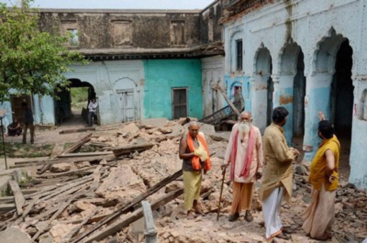 Ayodhya : Sadhus standing on the debris of a temple that collapsed following a tremor in Ayodhya on Saturday. PTI Photo  (PTI4_25_2015_000089B) *** Local Caption ***